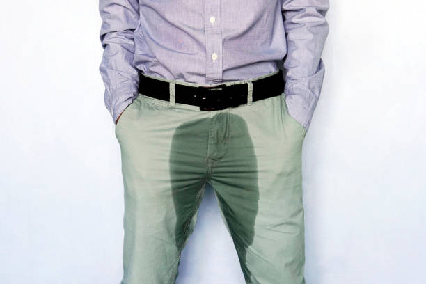 Problems with bladder. The concept of men's health. Young man in light trousers with wet stain from urine. stock photo
