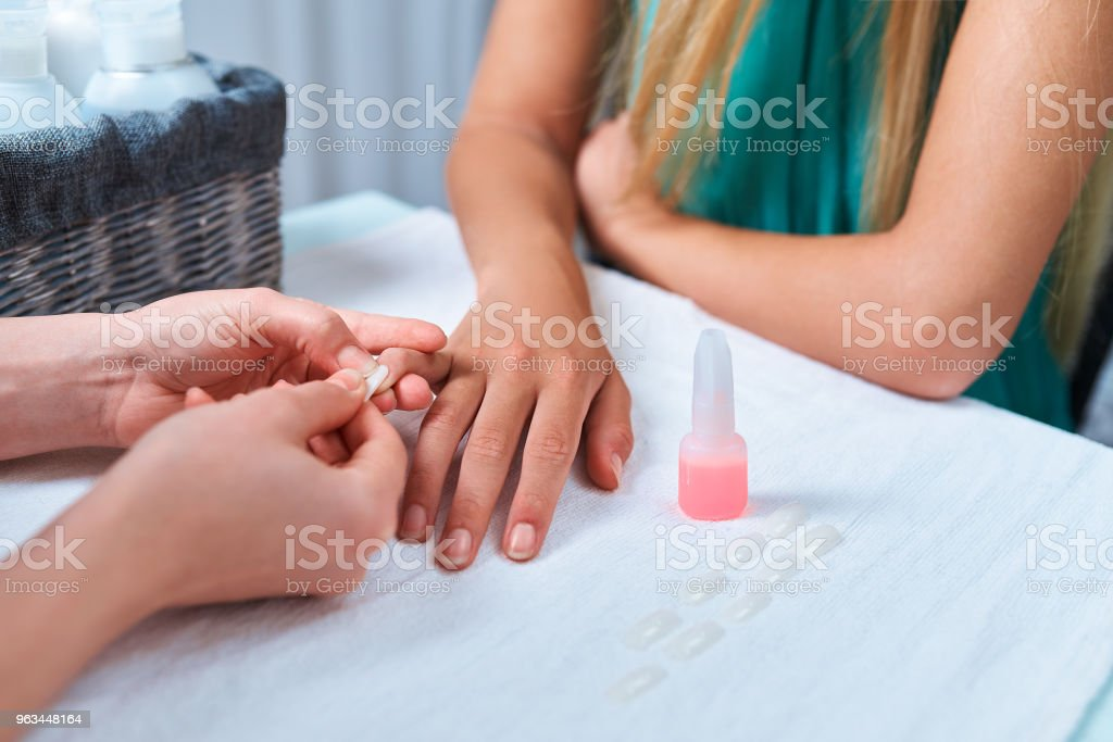 procedura klejenia sztucznych paznokci. manicure przykleja gwóźdź do palca klienta. - Zbiór zdjęć royalty-free (Butelka)