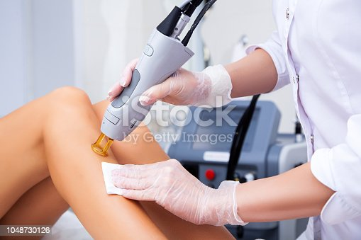 Close-up of a female cosmetologist in a medical coat making a young woman  a procedure laser hair removal for leg. Cosmetology, ionization, diamond procedures.