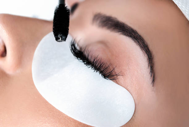 Procedure placed silk eyelashes on girl in beauty salon, close up Applying process Extension silk eyelashes on young woman in a beauty studio, close up. Make up concept. false eyelash stock pictures, royalty-free photos & images