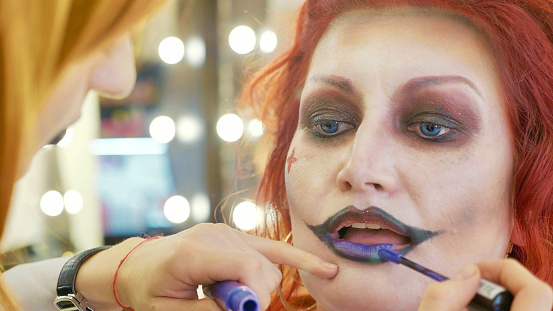 istock Process applying halloween makeup on face the woman in nurse style 868823178