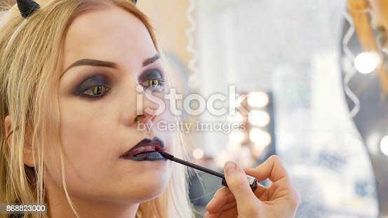 istock Process applying halloween makeup on face the young beautiful woman 868823000