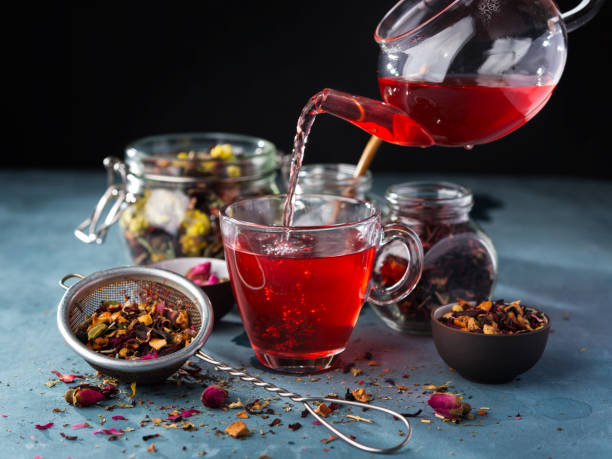 process brewing tea, tea ceremony, cup of freshly brewed fruit and herbal tea, dark mood. hot water is poured from the kettle into a cup with tea leaves. - herbata ziołowa zdjęcia i obrazy z banku zdjęć