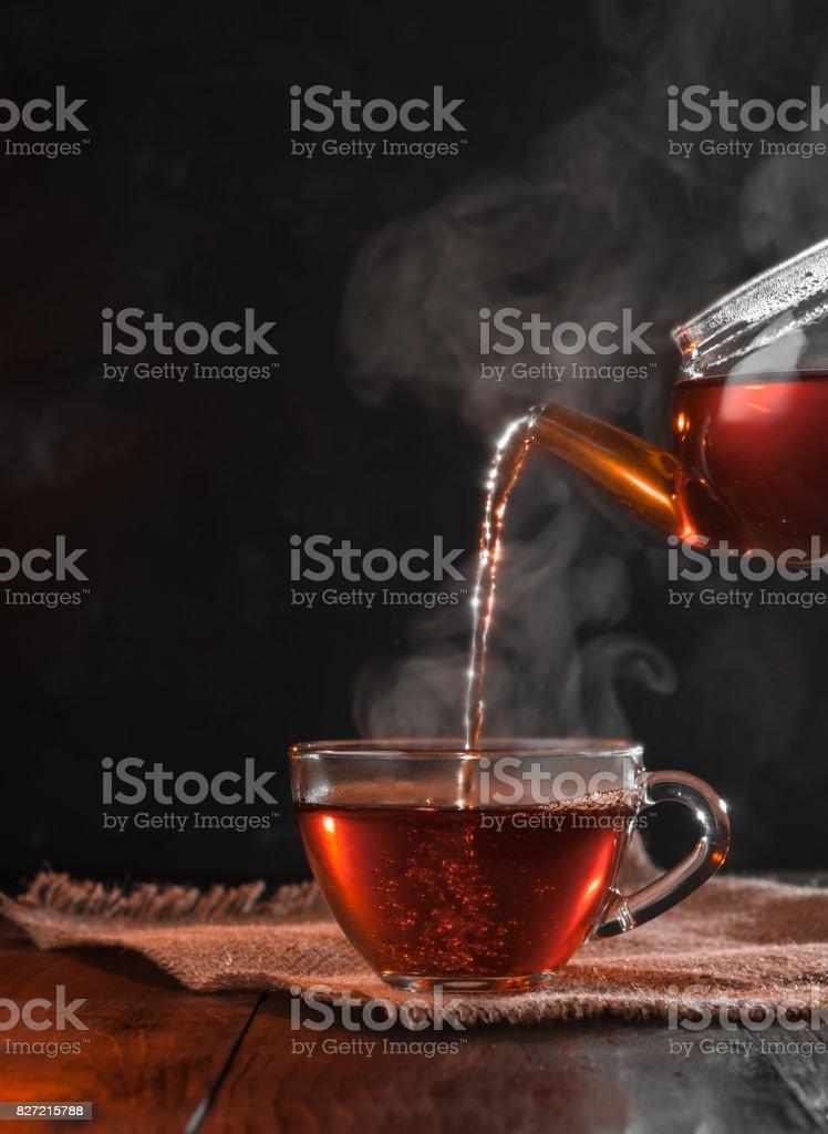 Process brewing tea,tea ceremony,Cup of freshly brewed black tea,warm soft light, darker background. stock photo