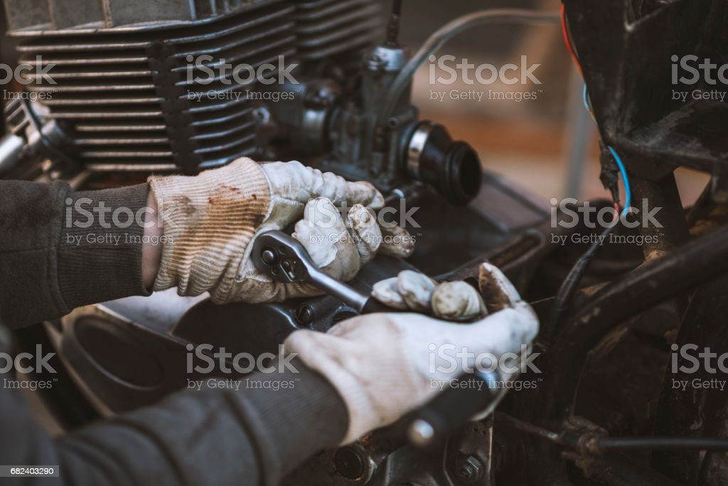 Process of caring and maintain an old motorcycle, retro royalty-free stock photo
