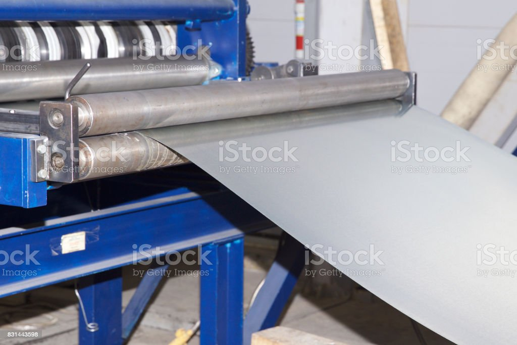 Process of cutting a wide sheet of metal into narrow strips on a machine stock photo