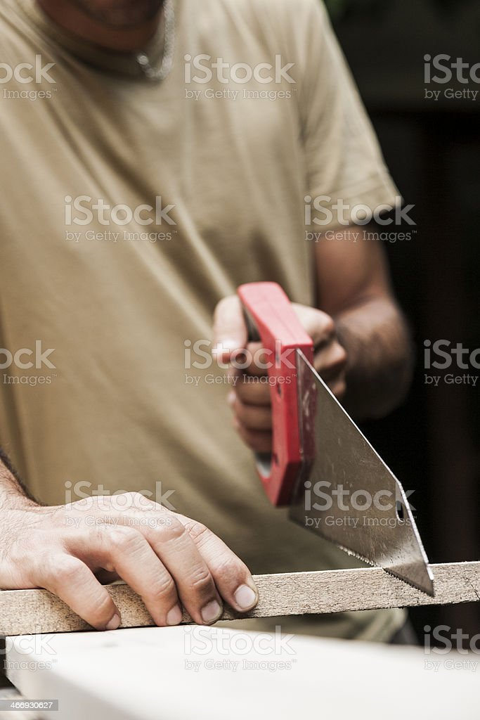 Process of cutting wooden board with saw royalty-free stock photo