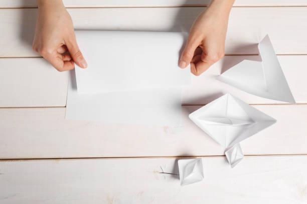 prozess der handarbeit von origami papierboot - origami anleitungen stock-fotos und bilder