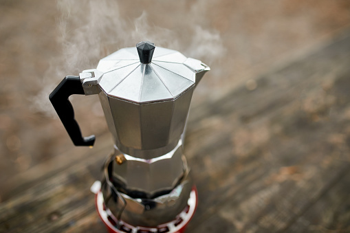 Process of making camping coffee outdoor with metal geyser coffee maker on a gas burner, step by step