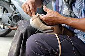 Process of manual shoe reparation, sole and welt fixing and stitching.