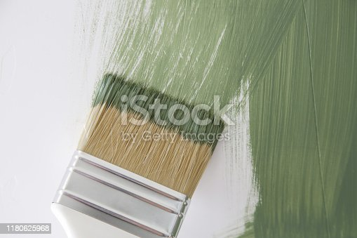 Process of painting wall with green color, paintbrush close up, DIY house improvement project