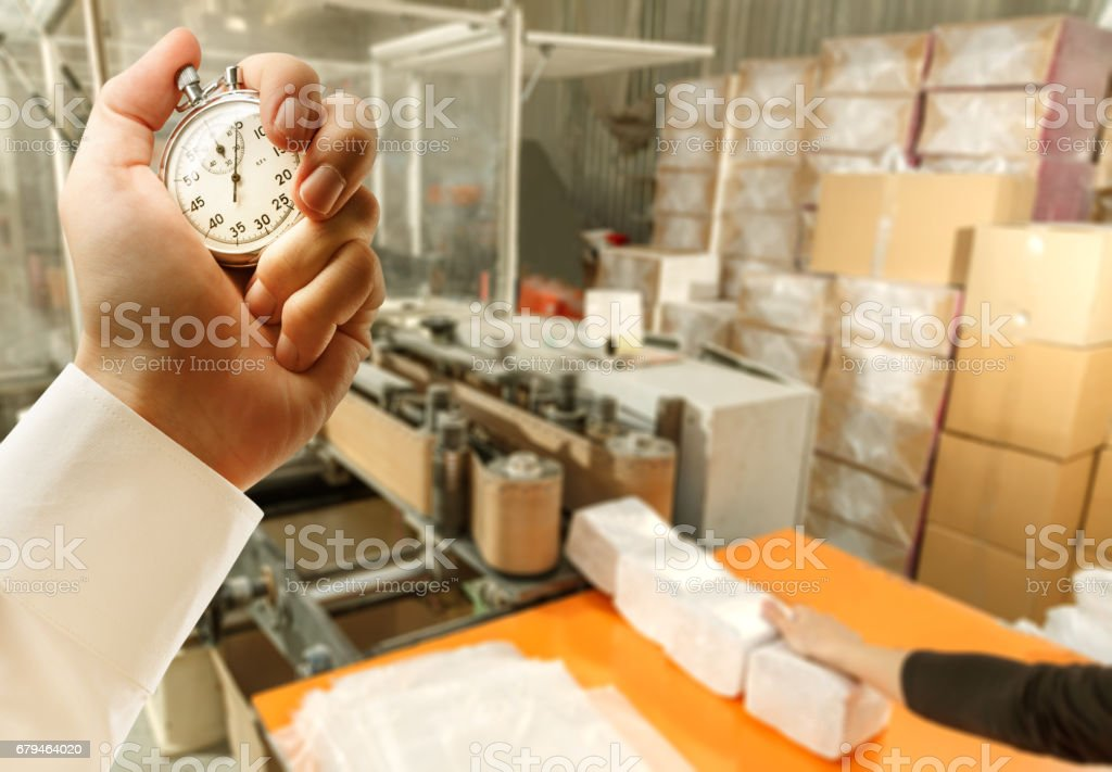 Process of paper products manufacturing and stopwatch in hand royalty-free stock photo