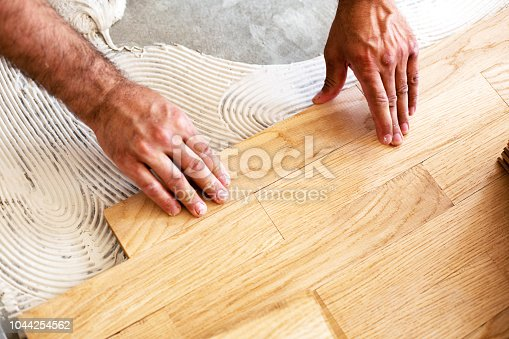 1124475954istockphoto Process of parquet alignment in a closeup mode 1044254562