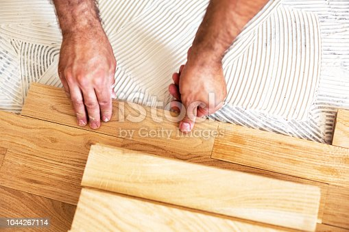 922081754istockphoto Process of parquet alignment in a closeup mode 1044267114