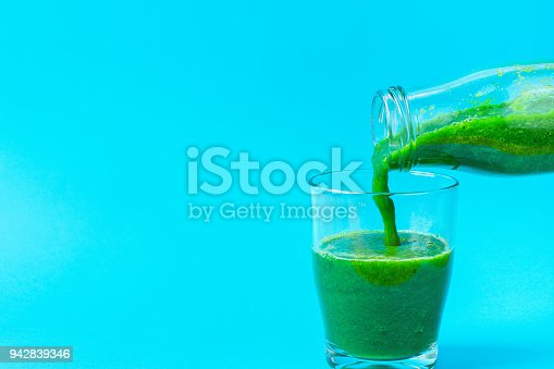 istock Process of Pouring from Bottle to Glass of Green Fresh Smoothie from Leafy Greens Vegetables Fruits. Apples Bananas Kiwi Zucchini Spinach on Light Blue Background. Healthy Lifestyle Detox Vitamins 942839346