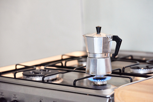 Process of preparing tasty aromatic ground coffee in metal coffee pot standing on stove and heating on fire in modern kitchen at home - Preparing italian caffe on a gas stove
