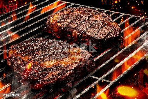 Process of preparing two pork or beef steaks. Meat roasted on metal portable summer barbecue BBQ grill with bright flaming fire, smoke and ember charcoal. Cooking and restaurant concept. Close up