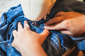 Process of repairing and sewing the jeans at home, close up of denim on the sewing machine, hemming, tailoring and stitching jeans cloth and dress, with the hand of female dressmaker