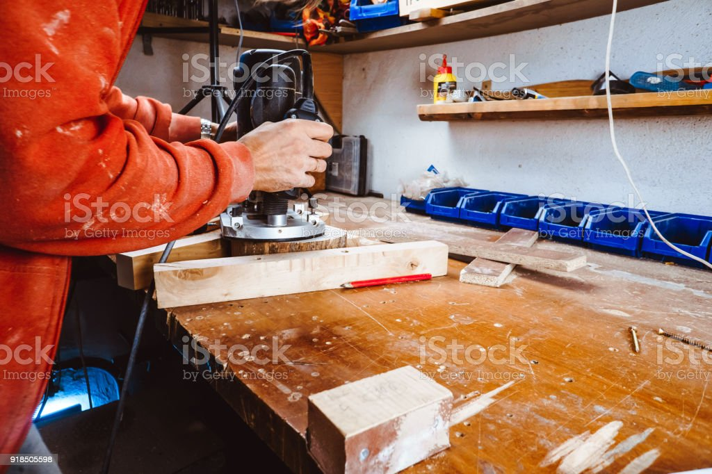 Processing of a furniture part by a machine for polishing a tree. the grinding machine on a board, selective focus. stock photo