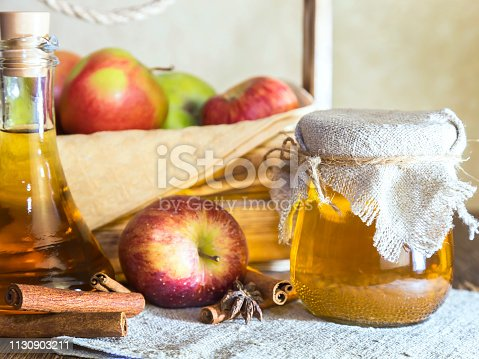 istock Processing of an agricultural crop of red and green apples. Home canning, healthy diet vegetarian food. Spiced apple cider vinegar, juice, cinnamon cider in a glass jar next to a box of ripe fruit 1130903211