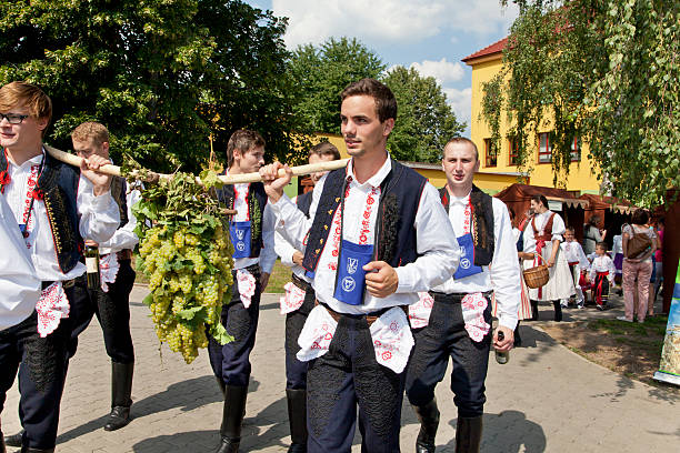 Procession on the feast of wine Polešovice, Czech Republic - August 22, 2015: Members of folk dance group from Southern Moravia in the Czech Republic come in front of the procession on the feast of wine. They carry the flag of the city and a big bunch of grapes on a stick. They are dressed in beautiful multicolor folk costumes from southern Moravia. The traditional ceremony took place in Polešovice in southern Moravia in the Czech repiblice. moravia stock pictures, royalty-free photos & images