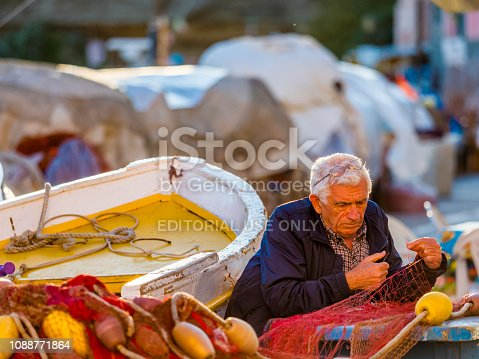 Procida Island in the Campania region of Italy on October 26, 2017: Elderly fisherman  mending traditional fishing nets by hand on Procida Island harbor