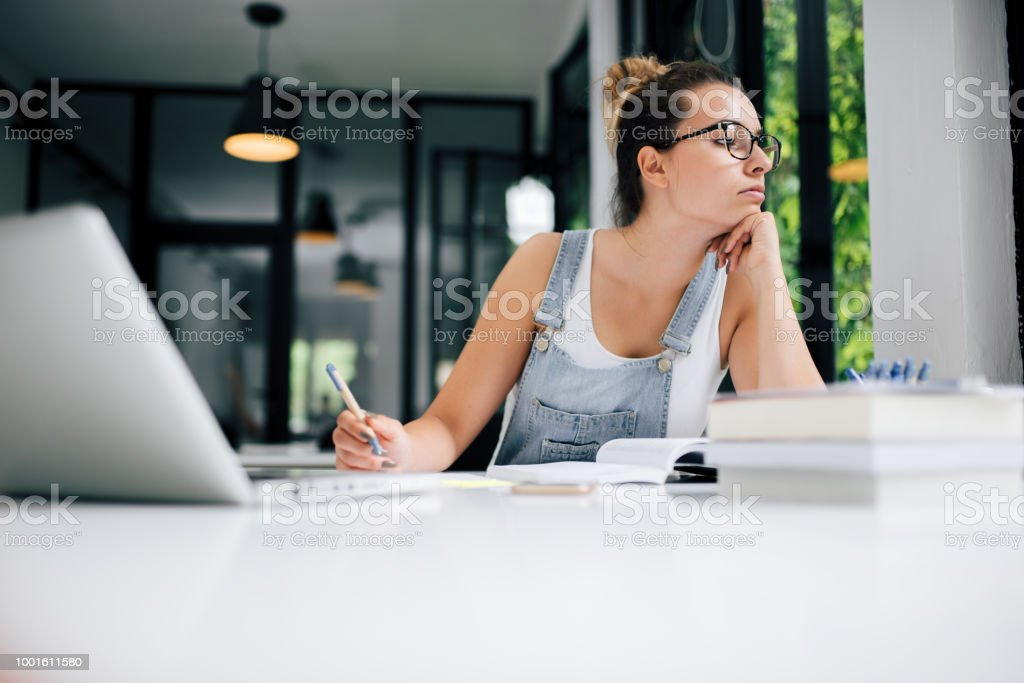 Procrastination concept. Girl looking away while studying. stock photo