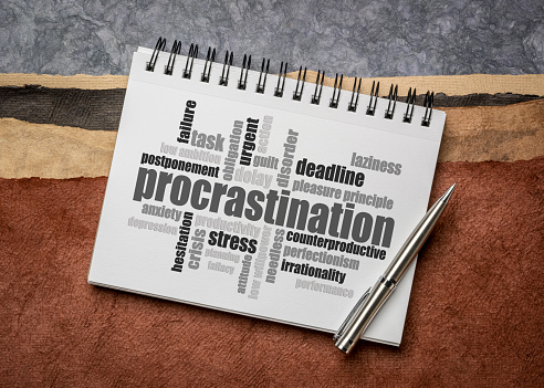 procrastination word cloud in a sketchbook against abstract paper landscape, productivity and personal development concept