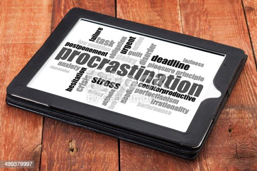 procrastination word cloud on a digital tablet against red grunge barn wood