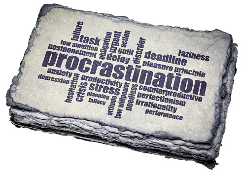 procrastination word cloud on a dark handmade paper, productivity and personal development concept