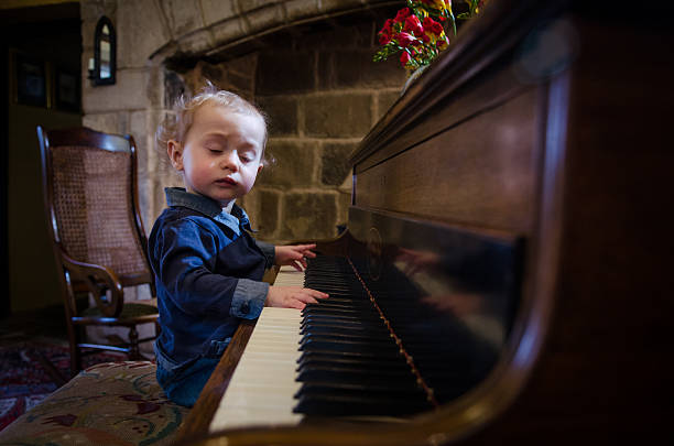 "Prodigy ""A very young child playing an antique piano, apparently completely lost in the music"" child prodigy stock pictures, royalty-free photos & images"