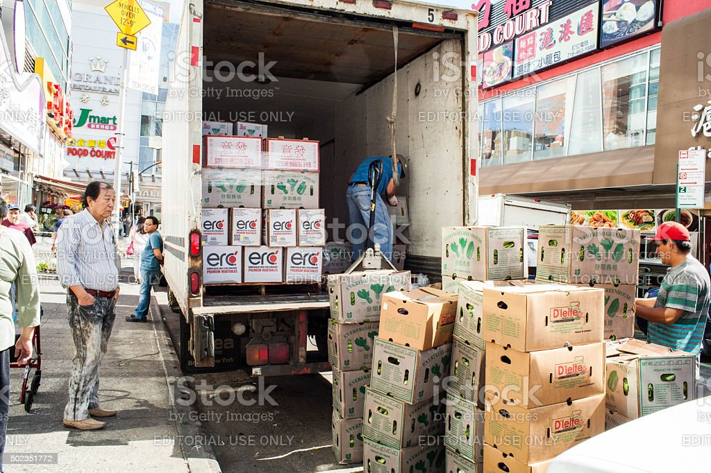 Produce being unloaded from back of truck in Chinatown stock photo