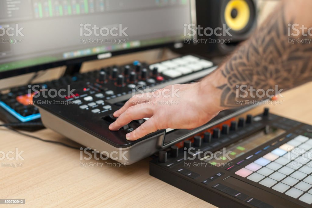Producer makes a music on MIDI keyboard stock photo