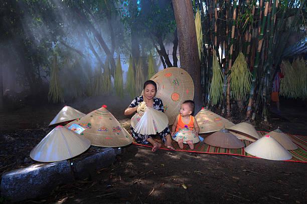 producing vietnamese traditional conical hats in a traditional handicraft village - königin kopfteil stock-fotos und bilder