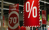 Product of the day -70%. Sale red signs in a clothing supermarket. More percent discounts price in a boutique window glass.