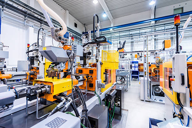 Production line of plastic industry Horizontal color image of large group of automated injection moulding machines for plastic parts production. construction machinery stock pictures, royalty-free photos & images