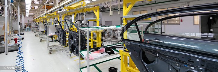 1069360792 istock photo Production of automobile doors. Long format. Wide angle view of plant of automotive industry. Can be used as banner 1072287424