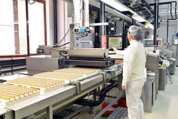 herstellung von pralinen in einer fabrik für die lebensmittelindustrie - conveyor belt arbeiter mit schokolade - nahrungsmittelfabrik stock-fotos und bilder