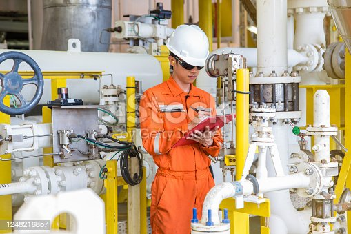 Production operator on offshore oil and gas central processing platform while checking and logging reading value of differential pressure gauge for process control system.