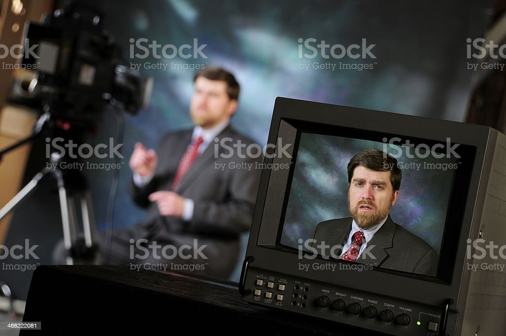 Production studio with man talking into television camera stock photo