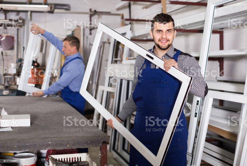 Trabalhadores de produção em combinação com diferentes perfis de PVC acabados e windows na fábrica - foto de acervo