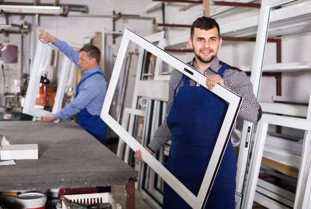 produktionsmitarbeiter im overall mit verschiedenen fertigen kunststoffprofile und fenster werkseitig - pvc stock-fotos und bilder