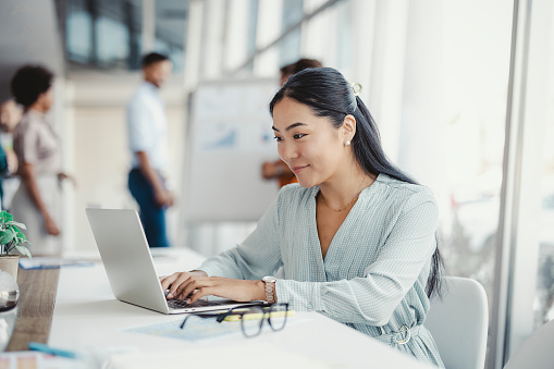 Asian woman working on laptop. Businesswoman busy working on laptop computer at office with colleagues in the background.