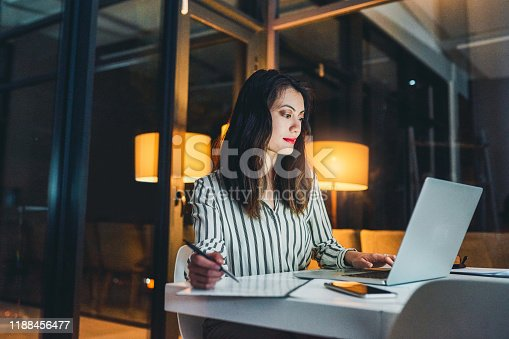 Shot of a young businesswoman using a laptop and writing notes during a late night at work