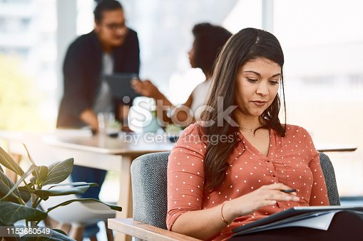 Shot of a young businesswoman using a digital tablet in a modern office