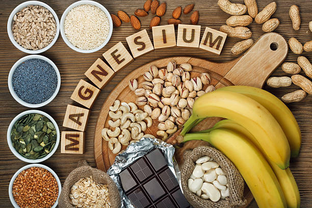 Products containing magnesium Products containing magnesium: bananas, pumpkin seeds, blue poppy seed, cashew nuts, beans, almonds, sunflower seeds, oatmeal, buckwheat, peanuts, pistachios, dark chocolate and sesame seeds on wooden table mineral stock pictures, royalty-free photos & images