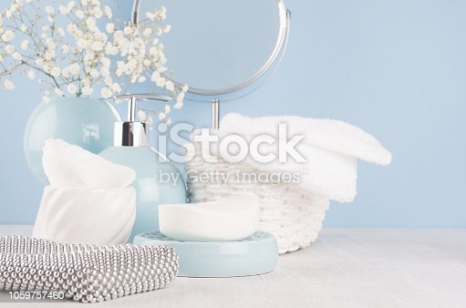1056636898 istock photo Products for body and skin care in light blue ceramic bowls, silver cosmetic bag, circle mirror and white flowers on wood table and pastel blue wall, closeup. 1059757460