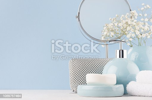 1056636898 istock photo Products for body and skin care in light blue ceramic bowls, silver cosmetic bag, circle mirror and white flowers on wood table and pastel blue wall. 1059757464