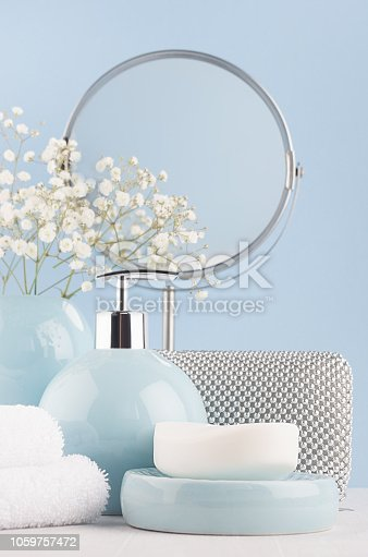 1056636898 istock photo Products for body and skin care in light blue ceramic bowls, silver cosmetic bag, circle mirror and white flowers on wood table and pastel blue wall, closeup, vertical. 1059757472