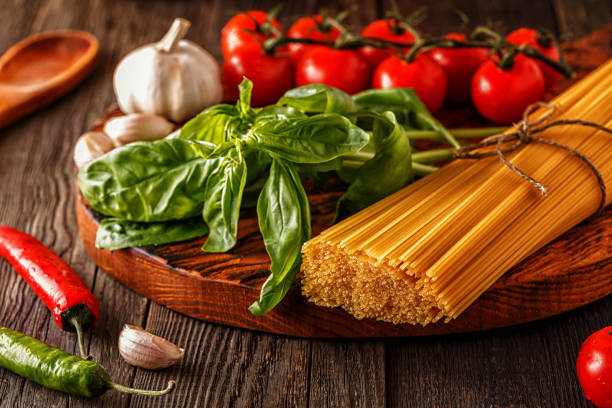Products for cooking - pasta, tomatoes, garlic, pepper, and basil stock photo